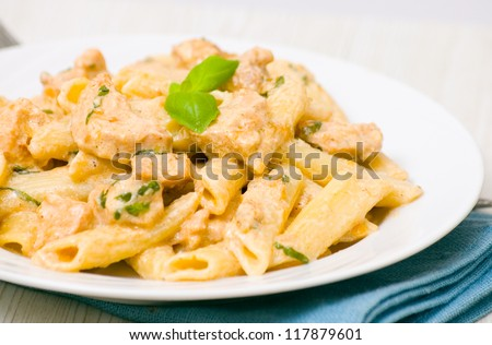 Penne pasta with chicken meat, cream sauce and basil - stock photo