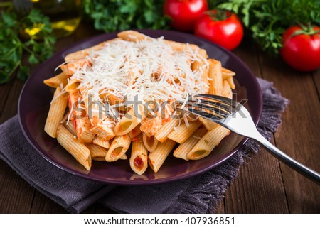 Penne pasta with chicken, tomato sauce and parmesan cheese on dark wooden background close up. Italian cuisine.  - stock photo