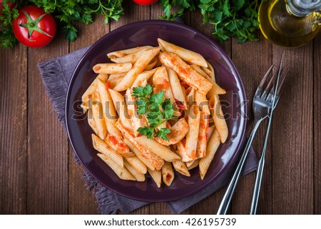 Penne pasta with chicken, tomato sauce and parsley on dark wooden background top view. Italian cuisine. - stock photo