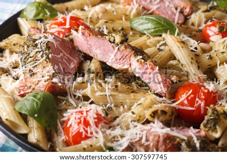 penne pasta with meat, tomato and pesto close up on a plate. Horizontal