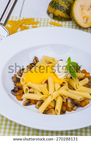 Penne pasta with pumpkin, tofu and mushrooms - stock photo
