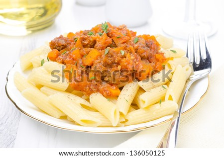 penne pasta with sauce of beef, tomato and pumpkin on a white plate, closeup