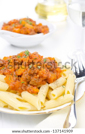 penne pasta with sauce of beef, tomato and pumpkin on the plate close-up and dressing in the background, vertical close-up