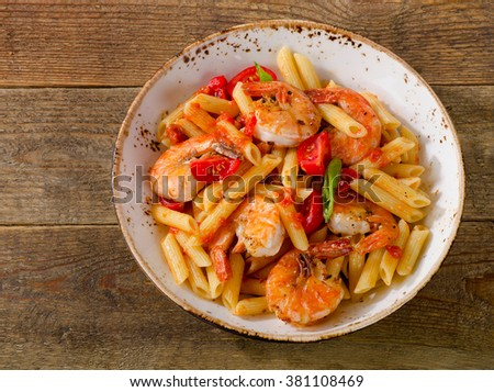 Penne pasta with shrimp and tomatoes  on rustic wooden table. Top view - stock photo