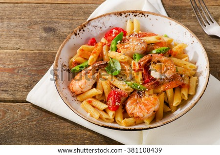 Penne pasta with shrimp, tomatoes and herbs on wooden background. Top view.  - stock photo