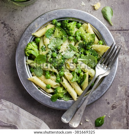 penne  pasta with spinach pesto sauce, green peas and broccoli,  top view, square image - stock photo