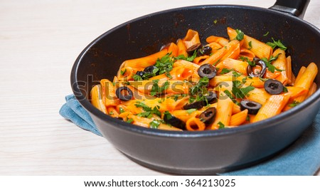 Penne pasta with tomato sauce in a frying pan - stock photo