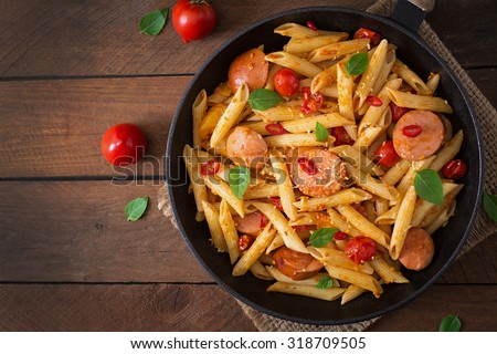Penne pasta with tomato sauce with sausage, tomatoes, green basil decorated in a frying pan on a wooden background. Top view - stock photo