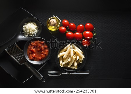 Penne pasta with tomatoes sauce and parmesan on black background - stock photo