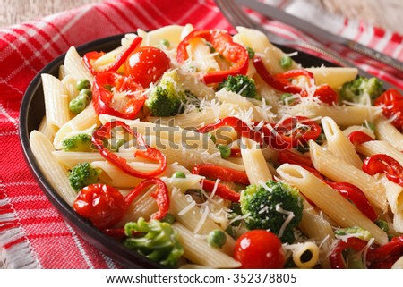 penne pasta with vegetables close-up on a plate on the table. horizontal