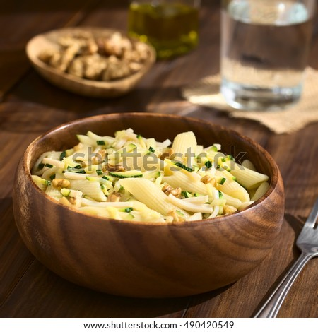 Penne pasta with zucchini and ham stripes and walnut served in wooden bowl, photographed on dark wood with natural light (Selective Focus, Focus in the middle of the dish)