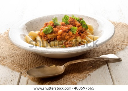 penne rigate with tomato sauce, minced meat and parsley