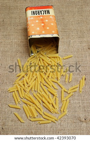 Penne scattered from vintage canister on burlap