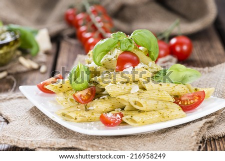 Penne with Basil Pesto, Parmesan Chesse and Tomatoes (close-up shot) - stock photo