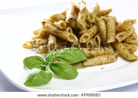 Penne with pesto decorated with basil - stock photo