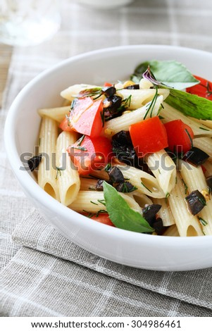 penne with slice of red tomatoes in white bowl