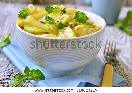 Penne with zucchini and mint on wooden table.