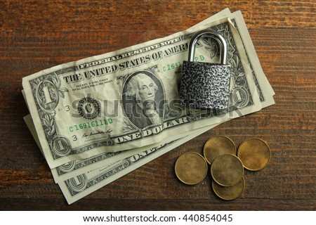 pennies and crumpled dollars with a small padlock on a brown wooden background.The concept of poverty