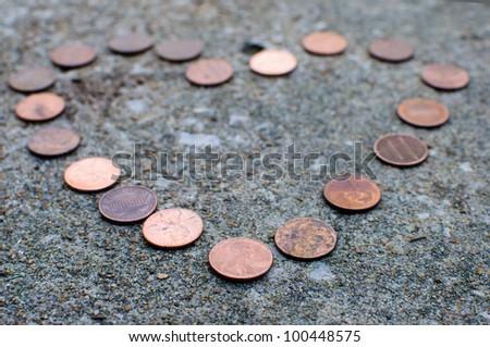 Pennies form a heart shape. - stock photo