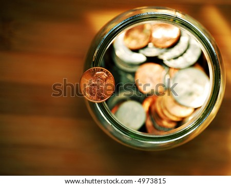 penny balancing on a jar full of coins