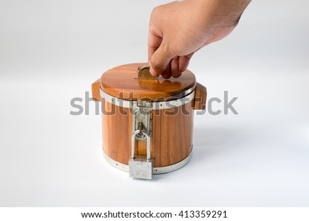 penny drops money into savings wooden - stock photo