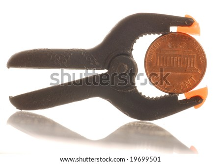penny squeezed in a clamp - penny pinching - stock photo