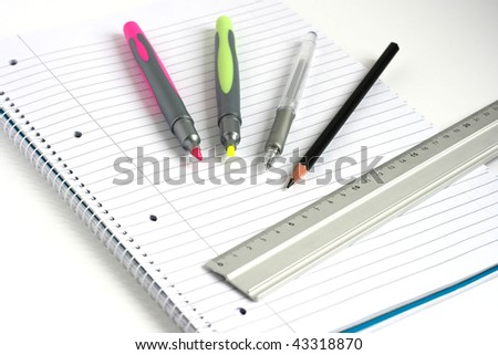 pens pencil and ruler on white lined notepad