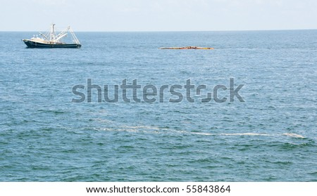 PENSACOLA BEACH - JUNE 23:  A boat skimming oil off the shore area is shown on June 23, 2010 near Pensacola Beach, FL - stock photo