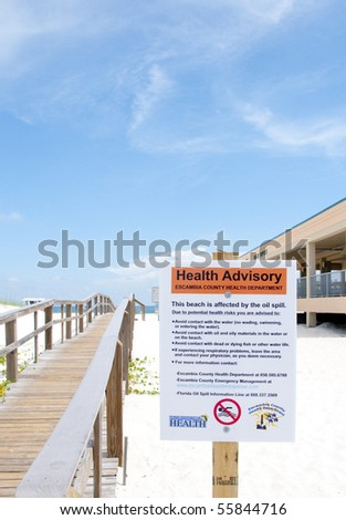 PENSACOLA BEACH - 23 JUNE:  A warning sign at the entrance to Pensacola Beach, FL warns swimmers on June 23, 2010 that the Gulf of Mexico waters are closed due to the BP oil spill. - stock photo