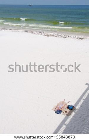 PENSACOLA BEACH - JUNE 23:  An unidentifed beachgoer lies on the sand on June 23, 2010 in Pensacola Beach, FL - stock photo