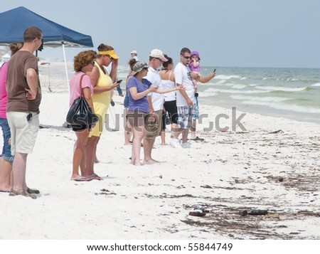 PENSACOLA BEACH - JUNE 23: Beachgoers stand near oil covered sand on June 23, 2010 in Pensacola Beach, FL - stock photo