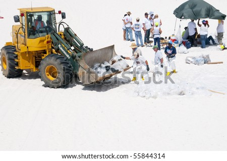 PENSACOLA BEACH - JUNE 23:  BP oil workers and heavy machinery work to remove oil covered sand on June 23, 2010 in Pensacola Beach, FL. - stock photo