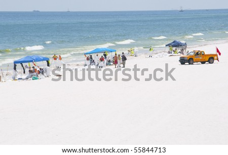PENSACOLA BEACH - JUNE 23:  BP oil workers and skimmer boats attempt to clean oil covered sand on June 23, 2010 in Pensacola Beach, FL. - stock photo