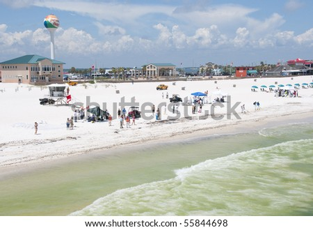 PENSACOLA BEACH - JUNE 23:  BP oil workers and tourists stand on the beach on June 23, 2010 in Pensacola Beach, FL. - stock photo