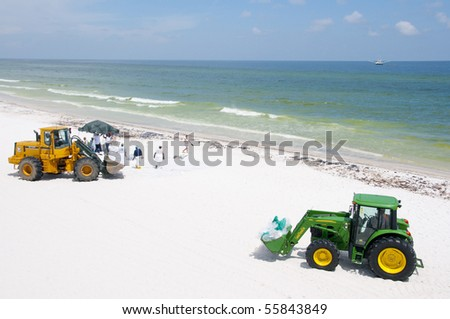 PENSACOLA BEACH - JUNE 23:  BP oil workers using heavy machinery attempt to clean oil covered sand on June 23, 2010 in Pensacola Beach, FL. - stock photo