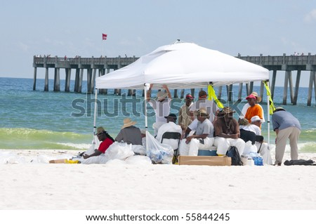 PENSACOLA BEACH - JUNE 23: BP workers attempt to clean oil off the beaches on June 23, 2010 in Pensacola Beach, FL - stock photo