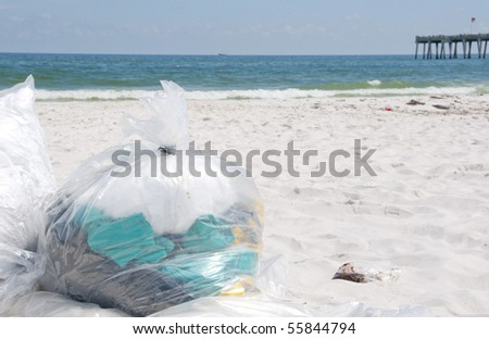 PENSACOLA BEACH - JUNE 23: Garbage bags filled with soiled rags lie on the beach on June 23, 2010 in Pensacola Beach, FL. - stock photo