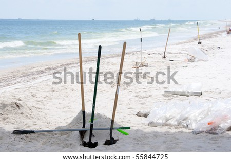PENSACOLA BEACH - JUNE 23: Large patches of oil wash ashore on Pensacola Beach, FL on June 23, 2010 at the height of the summer tourist season. BP worker shovels and debris bags dot the coastline. - stock photo