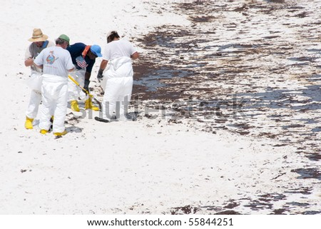 PENSACOLA BEACH - 23 JUNE:  Workers try to collect oil covered sand near the pier on June 23, 2010 in Pensacola Beach, FL. - stock photo