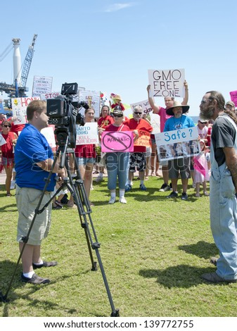 """PENSACOLA, FL - 25 MAY: Protesters in Pensacola, FL gather on May 25, 2013 to support worldwide """"March Against Monsanto"""" rallies over GMO (genetically modified) foods and lack of labeling. - stock photo"""