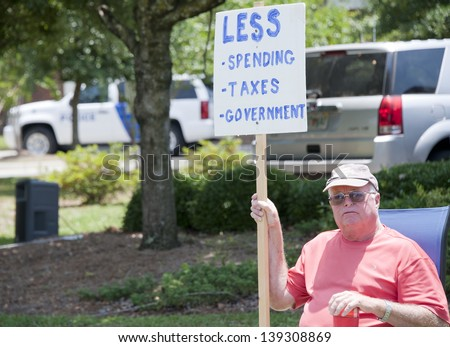 PENSACOLA, FL - 21 MAY: Protesters rally in front of local IRS office in Pensacola, FL on May 21, 2013 in response to news that conservative groups like the Tea Party were harassed by IRS officials. - stock photo