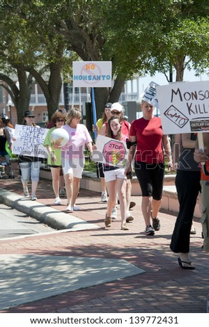 """PENSACOLA, FL - 25 MAY: Protesters rally in Pensacola, FL on May 25, 2013 in support of the worldwide """"March Against Monsanto"""" rallies to protest the safety and non-labeling of GMO foods. - stock photo"""