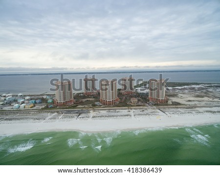 PENSACOLA, FLORIDA - APRIL 13, 2016: Flying over Gulf of Mexico and Portofino Island Resort Buildings with sandy beach in Pensacola.