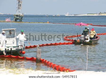 PENSACOLA - JUNE 10:  Oil spill workers clean the beach of Naval Air Station Pensacola, FL as oil washes ashore from the BP spill on June 10, 2010 in Pensacola, Florida. - stock photo