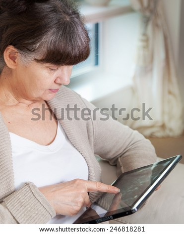 Pension age good looking woman searching in internet on tablet device