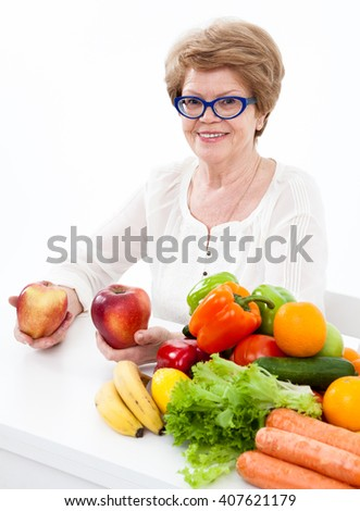 Pension age woman holding two red apples in hands, sitting with fresh fruit and vegetables on table, white background - stock photo
