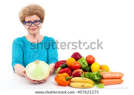 Pensioner age woman holding cabbage in hands, fresh fruit and vegetables on table, isolated on white background - stock photo