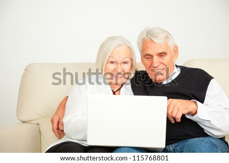 pensioner couple with computer - stock photo