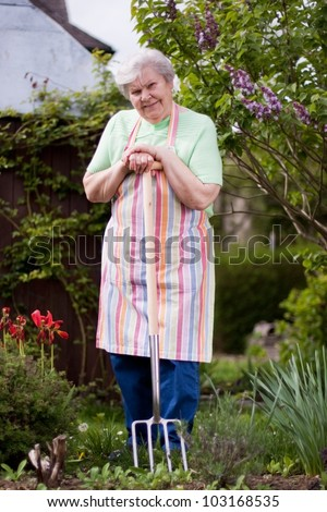 Pensioner in the garden with pitchfork - stock photo