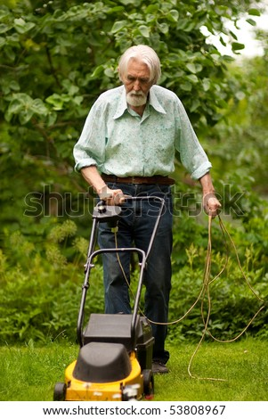 Pensioner mows grass lawn-mower on personal plot.